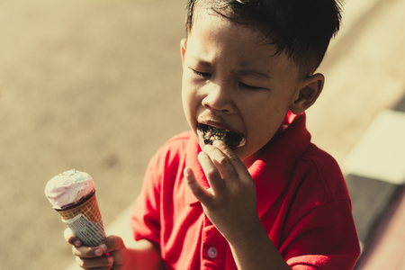 Kid eating ice cream in waffles cone and winking on park outdoor background. 免版税图像 - 124964554
