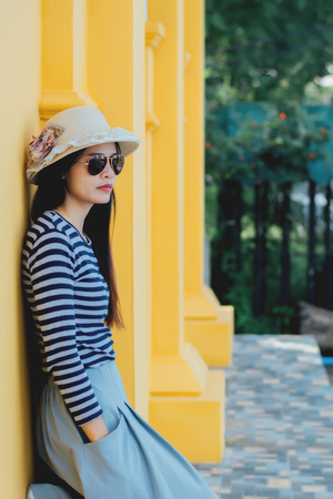 Sunny lifestyle fashion portrait of young stylish hipster woman beside building against yellow background, wearing trendy outfit, hat, travel concept. Imagens
