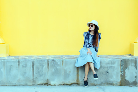 Sunny lifestyle fashion portrait of young stylish hipster woman beside building against yellow background, wearing trendy outfit, hat, travel concept. 免版税图像 - 124964637