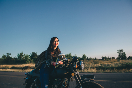 Young woman drive with motorbike on street, enjoying freedom and active lifestyle, having fun on a bikers tour.