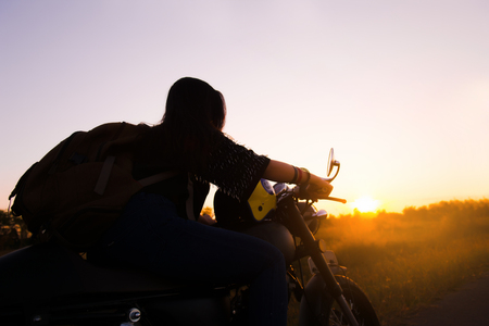 Silhouette of young woman drive with motorbike on street, enjoying freedom and active lifestyle, having fun on a bikers tour. 免版税图像