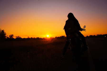 Silhouette of young woman drive with motorbike on street, enjoying freedom and active lifestyle, having fun on a bikers tour. Stock Photo