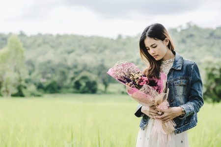 Young woman in a field ,flower holder having fun outdoor in countryside.Awesome warm summer day.
