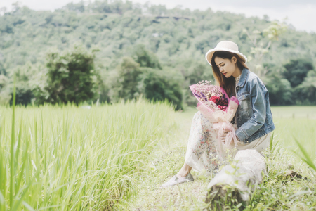 Young woman in a field ,straw hat and flower having fun outdoor in countryside.Awesome warm summer day.