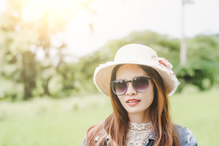 Young woman in a field , rounded sunglasses having fun outdoor in countryside.Awesome warm summer day. 免版税图像 - 124964849