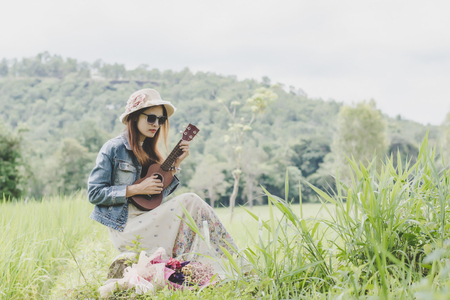 Young woman in a field , rounded sunglasses and straw hat and ukulele having fun outdoor in countryside.Awesome warm summer day. Stock Photo