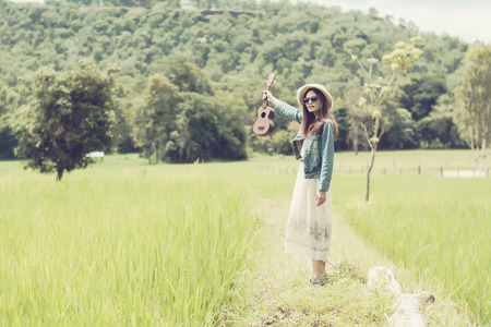 Young woman in a field , rounded sunglasses and straw hat and ukulele having fun outdoor in countryside.Awesome warm summer day. 免版税图像 - 123514344