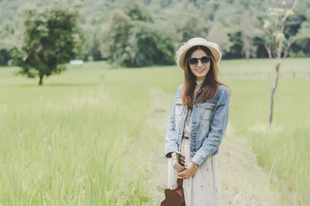Young woman in a field , rounded sunglasses and straw hat and ukulele having fun outdoor in countryside.Awesome warm summer day. 免版税图像