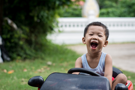 Little boy driving car with the steering wheel. Boy in a white shirt in a red toy car in the street. Little boy driving big toy car and having fun, outdoors. 免版税图像 - 124969500