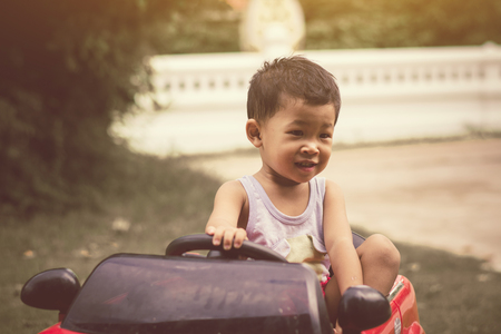 Little boy driving car with the steering wheel. Boy in a white shirt in a red toy car in the street. Little boy driving big toy car and having fun, outdoors. 免版税图像 - 124969546
