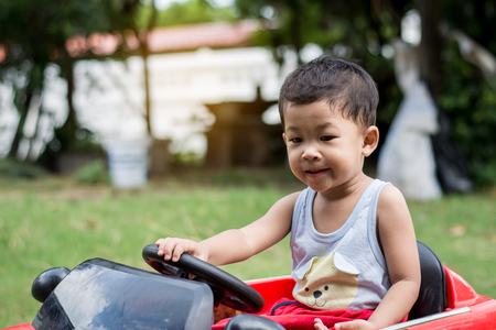 Little boy driving car with the steering wheel. Boy in a white shirt in a red toy car in the street. Little boy driving big toy car and having fun, outdoors.