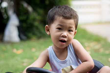 Little boy driving car with the steering wheel. Boy in a white shirt in a red toy car in the street. Little boy driving big toy car and having fun, outdoors. 免版税图像 - 124969901