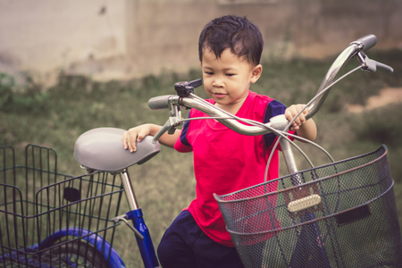 Happy children playing with a bike alone.