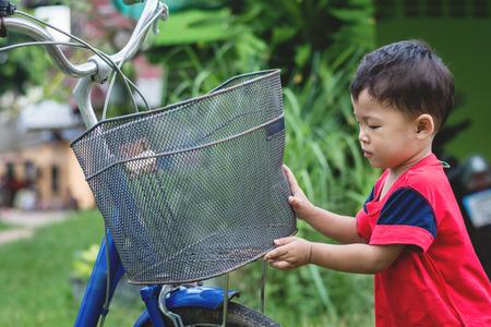 Happy children playing with a bike alone. 免版税图像 - 123507930
