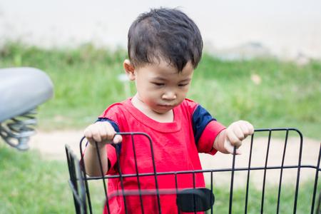 Happy children playing with a bike alone. 免版税图像 - 123508436