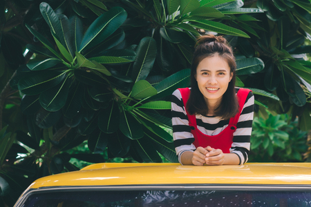 Close up portrait of hipster woman with her yellow car in green background, Hobby concept.