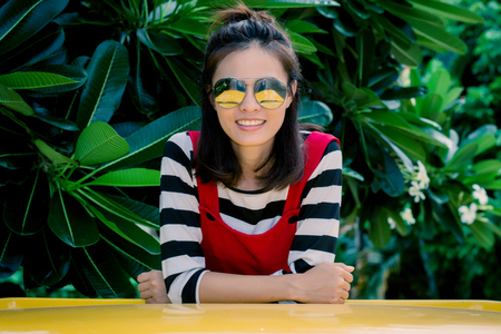 Close up portrait of hipster woman with her yellow car in green background, Hobby concept. 免版税图像 - 123513931