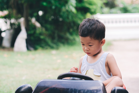 Little boy driving red car with the steering wheel. Little boy driving big toy car and having fun on grass outdoors.
