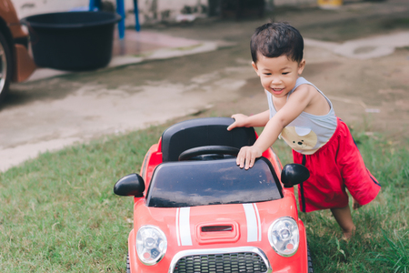 Little boy driving red car with the steering wheel. Little boy driving big toy car and having fun on grass outdoors. 免版税图像 - 125881145