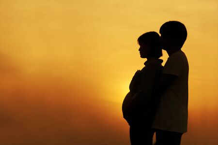 Silhouette of a couple Pregnant couple hug and holding belly talking with their child on sunset background.