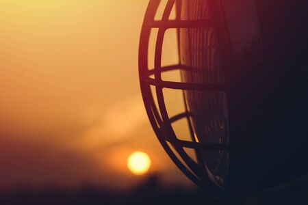 Close-up of motorcycle headlight on sunset background. 免版税图像