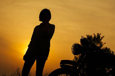 Silhouette of biker woman and motorcycle parking with sunset background.Tip and lifestyle of motorbike concept.