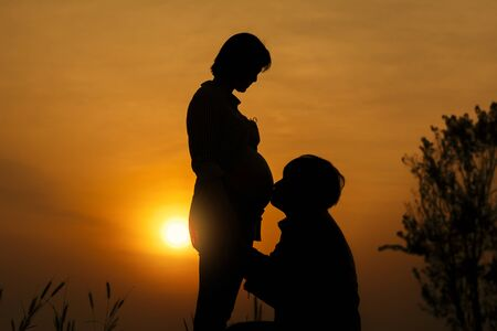 Silhouette of Young man kissing his pregnant wife's belly and talking with their child on sunset background. 免版税图像