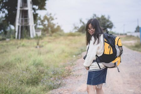 Asian women traveling alone with backpack and camera.Travel Holiday Relaxation Concept , Vintage Style.