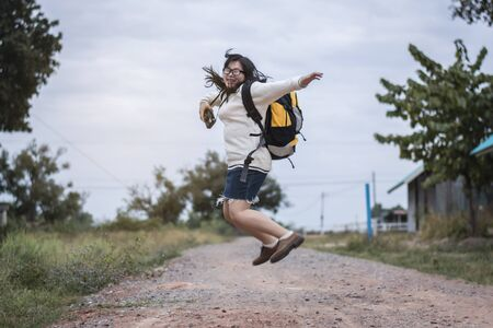 Asian women traveling alone with backpack and camera. She is jumping.Travel Holiday Relaxation Concept , Vintage Style.