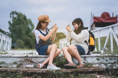 Two trendy cool hipster girls, friends, on the old wooden bridge, and backpacks, holding vintage camera, positive emotions. 免版税图像