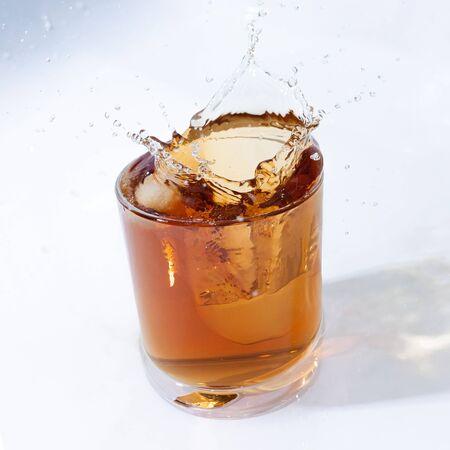 whiskey cocktail with cola and ice in a transparent glass with beautiful splashes Standard-Bild