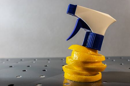 air freshener and window cleaner and lemon on a metal surface