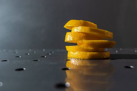 yellow juicy lemon wedges on a metal surface with hard light on a gray background