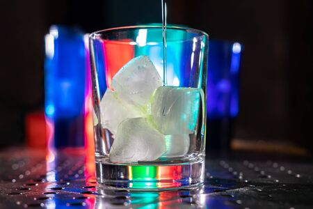green cocktail with vodka gin rum sambuca tequila and pieces of ice on a bar in a nightclub with colored lights