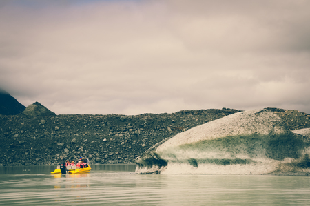 tasman: A Yellow Boat Glacier Cruise in Tasman Lake on a Cloudy Day with Vintage Colour Effects Stock Photo