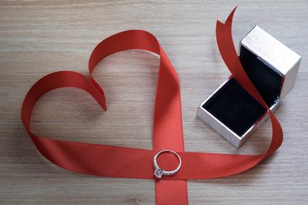 matrimonio feliz: Anillo de bodas y cinta roja del corazón en superficie de madera para San Valentín o propuesta de matrimonio Foto de archivo