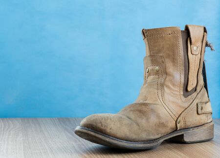 footware: Patina Engineer Leather Boot on wooden surface and blue background with space for text