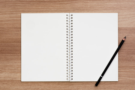 spiral binding: Opened blank ring spiral binding notebook with a pencil on wooden surface, writing concept, your own contents, space for text