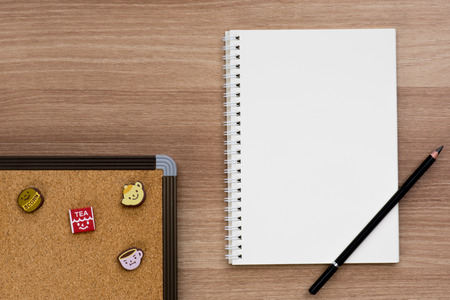 spiral binding: Opened blank ring spiral binding notebook with a pencil and cork board with cute push pins of tea break concept on wooden surface, writing concept, your own contents, space for text
