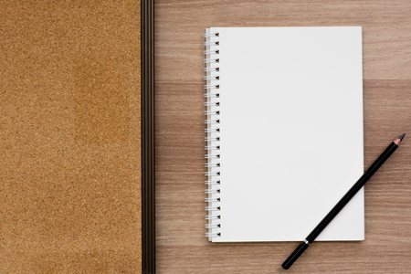 spiral binding: Opened blank ring spiral binding notebook with a pencil and cork board on wooden surface, writing concept, your own contents, space for text