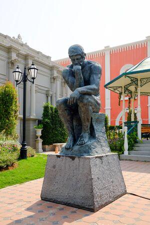 man sitting statue on the public park thailand