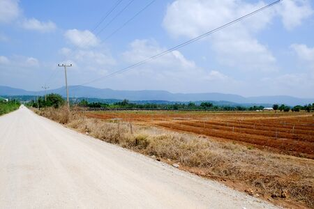 rural road with desolate field and blue sky