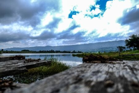 wood pier foreground with lake mountain and sky background 免版税图像