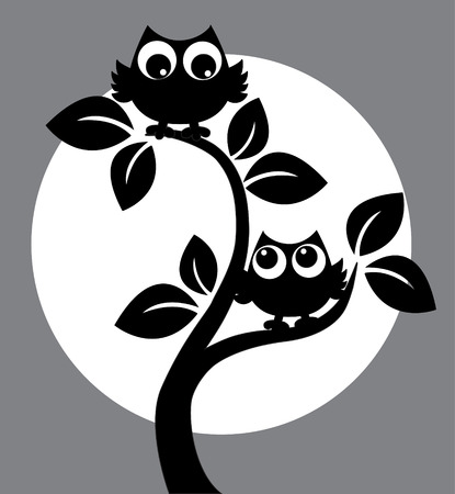 silhouette of two black owls in a tree