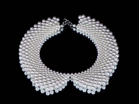dress form: pearl necklace on a black background in the form of a collar for the dress