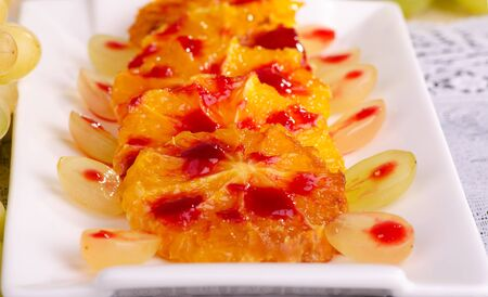 caramelized: colorful dessert, caramelized oranges with grapes and raspberry sauce