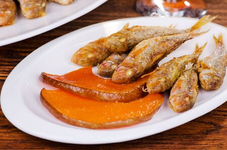 mullet: fried fish, red mullet with a pumpkin on a white plate