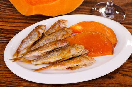 mullet: fried fish, red mullet with a pumpkin and a glass of wine on a wooden table Stock Photo