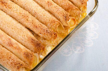 maslenitsa: Rolled pancakes with crispy crust in baking dish