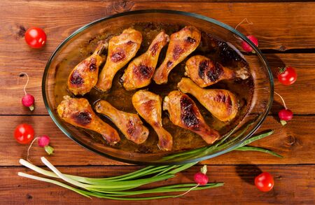 oval shape: Chicken legs baked in an oval shape on a wooden background with vegetables, top view.